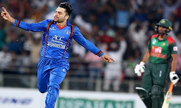In this photo taken on June 3, 2018, Afghan cricket player Rashid Khan (L) celebrates the wicket during the first Twenty20 International cricket match between Afghanistan and Bangladesh at Rajiv Ghandi International Cricket Stadium in Dehradun. (Photo by Kamal Sharma / AFP) (Photo credit should read KAMAL SHARMA/AFP/Getty Images)